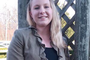 Elisabeth Brockman stands in front of a garden grate for mugshot.