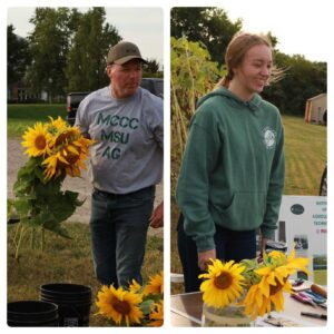 Andy holds sunflowers, Josie stands at the sale table