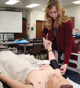 Holly Boylan administers a blood pressure cuff to a medical mannequin
