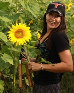 Stacy Thomas holds a sunflower and a pair of shears in her hand, smiling at the camera.