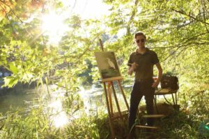 Brant Georgia stands in a shady area on the bank of River Raisin in front of an easel.